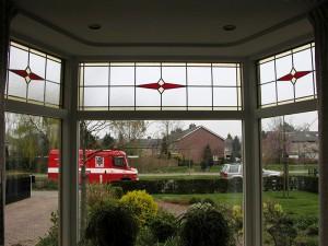 glas in lood, gemaakt naar bestaand glas in de woning - bedrijfsbus op de achtergrond
