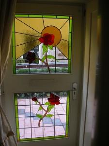 roosmotieven en zon in buitendeur, eigen ontwerp