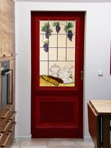 raam in schuifdeur, het brandschilderwerk is naar wens van de opdrachtgevers geïnspireerd op Olivier B Bommel